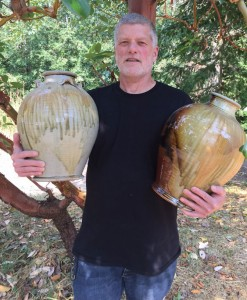 artist holding two vases he made