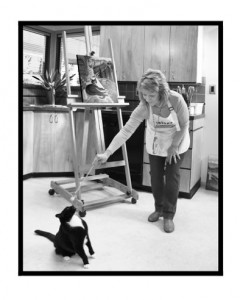 artist in her studio with a cat