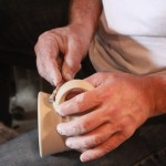 artist's hands smoothing ing the clay