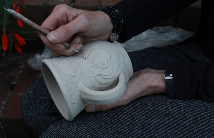 artist using a tool to carve clay