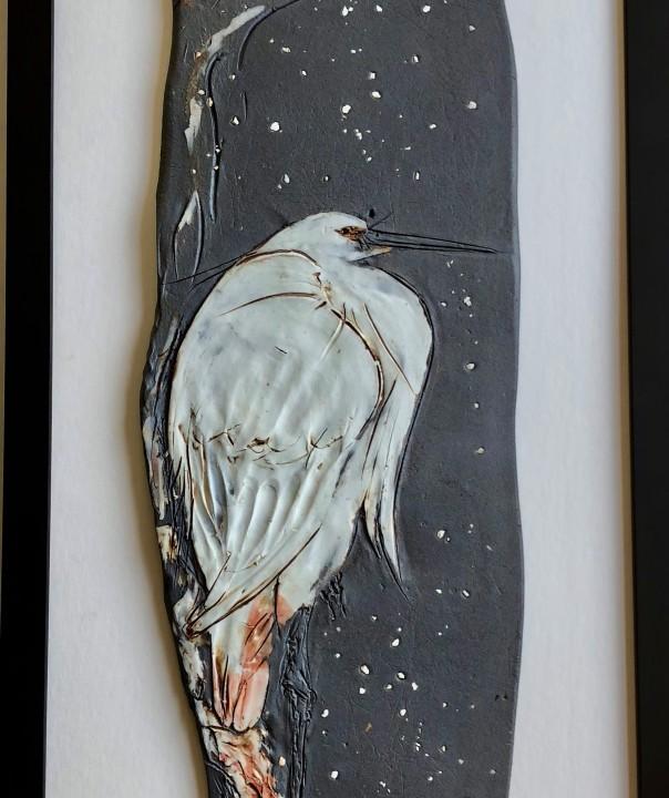 white heron perched on a limb