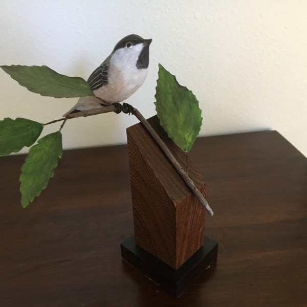 chickadee on a carved branch