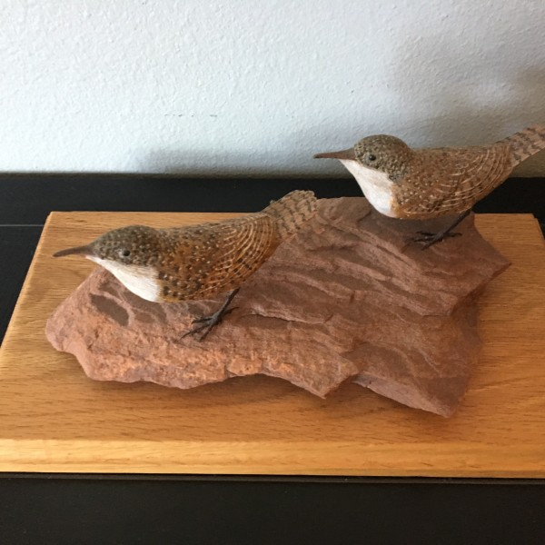 2 carved birds on wood