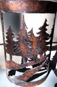 rusty metal piece with trees and creek cut in the metal