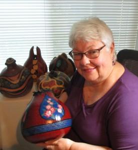 artist holding carved gourd