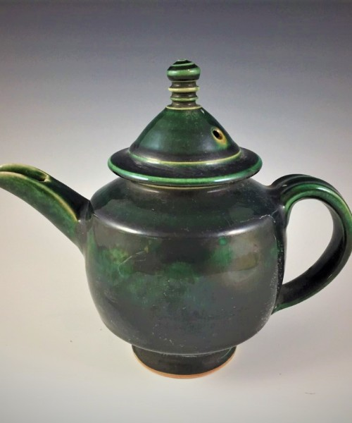 Dark colored tea pot with a lid