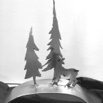 two elongated trees with a deer on a curved metal stand