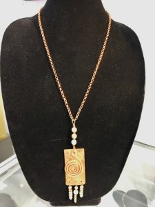 Long rectangular copper piece with coiled copper and white round clay beads.