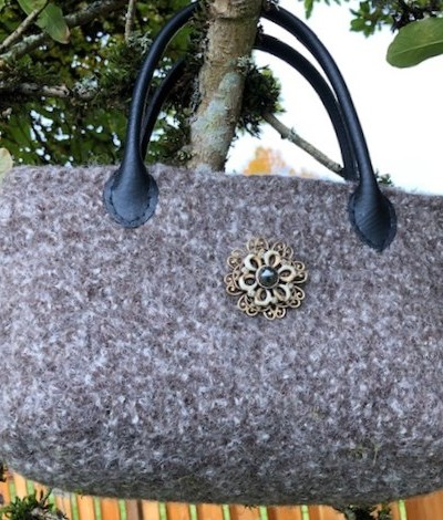 gray purse with handles and pin